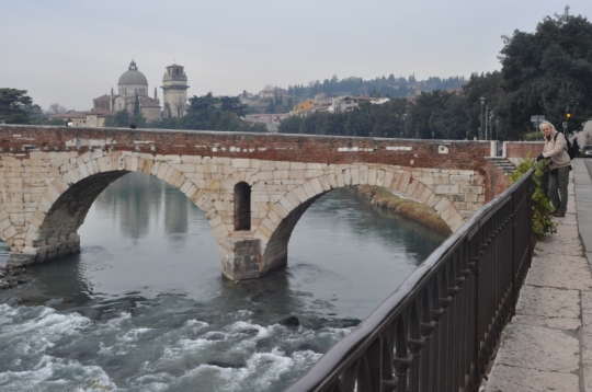 """ponte pietra bridge The Ponte Pietra (Italian for """"Stone Bridge""""), once known as the Pons Marmoreus, is a Roman arch bridge crossing the Adige River in Verona, Italy. The bridge was completed in 100 BC, and the Via Postumia from Genua to the Brenner Pass passed over it. It originally flanked another Roman bridge, the Pons Postumius; both structures provided the city (on the right bank) with access to the Roman theatre on the east bank. The arch nearest to the right bank of the Adige was rebuilt in 1298 by Alberto I della Scala. Four arches of the bridge were blown up by retreating German troops in World War II, but rebuilt in 1957 with original materials. source: wikipedia"""